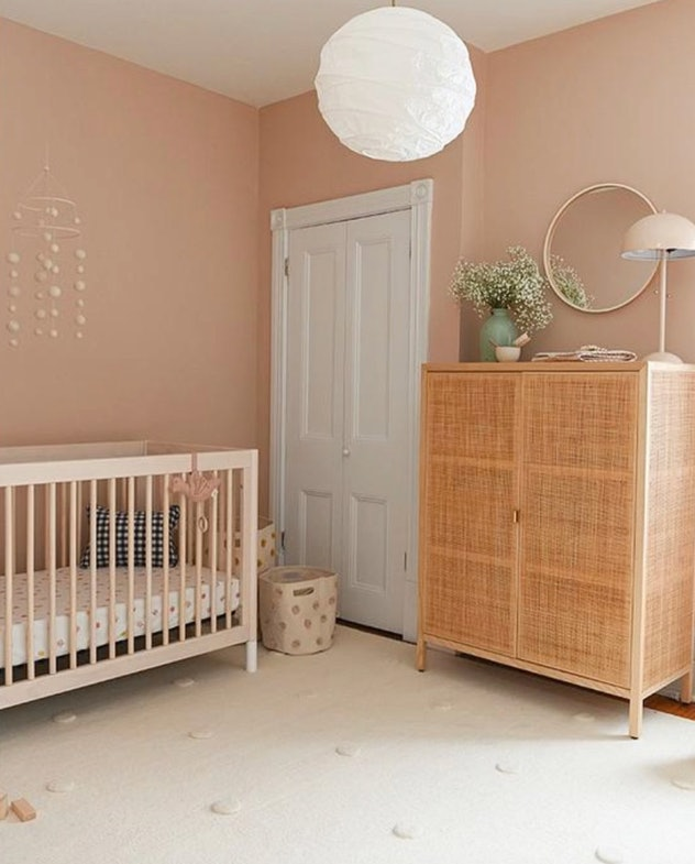 baby nursery with blush walls and cane and wooded accents