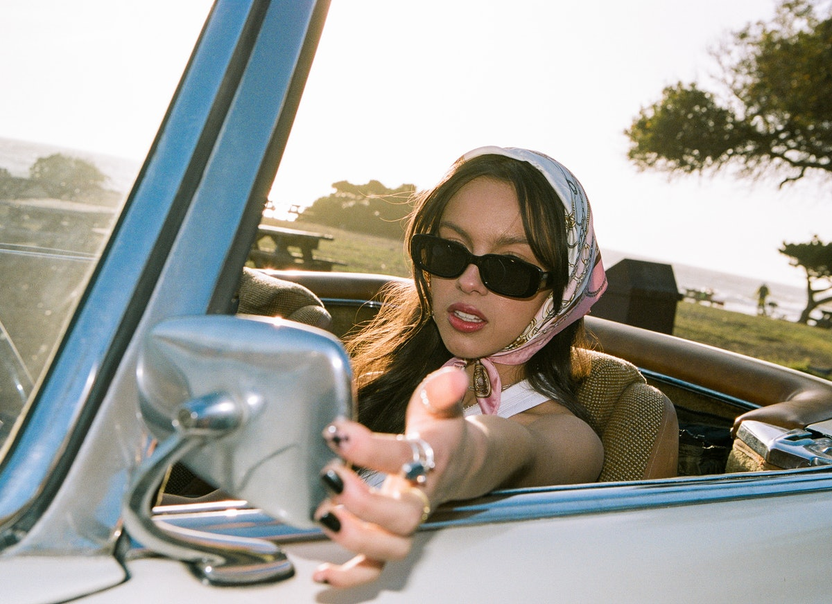 """Olivia Rodrigo sitting in a car wearing items from her """"deja vu"""" music video, which she is selling on Depop"""