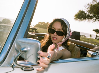 """Olivia Rodrigo sitting in a car wearing items from her """"deja vu"""" music video, which she is selling o..."""