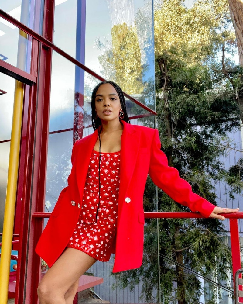 Tessa Thompson poses in a red dress and blazer.