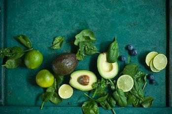 berries, avocados, limes, berries on dark background