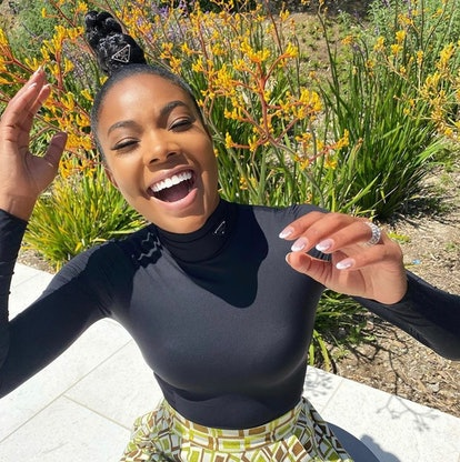 Gabrielle Union laughing outside with white cloud French manicure