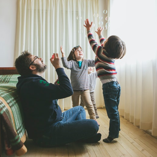dad blowing bubbles with kids