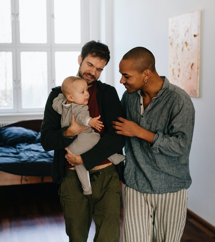 Gay fathers leaving bedroom together carrying newborn son