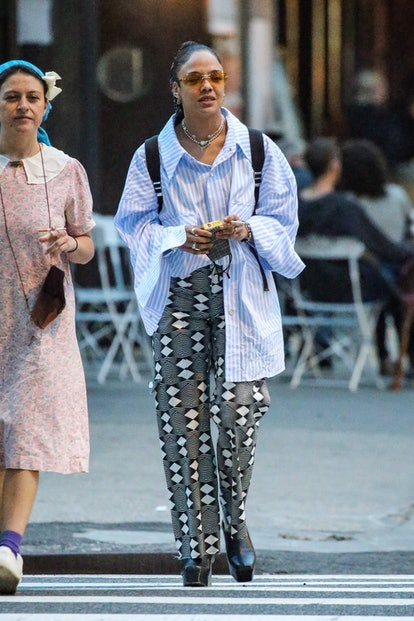 Tessa Thompson wearing a half-tucked stripe shirt and patterned pants while walking around in New York City on June 2, 2021.