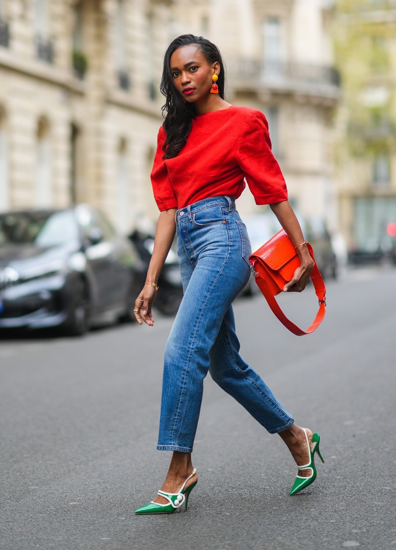 PARIS, FRANCE - APRIL 18: Emilie Joseph @in_fashionwetrust wears a red vintage linen power shoulder top worn backwards with plunging neckline in the back, blue denim high rise straight ribcage jeans from Levi's, green two-toned patent leather pointy sling back sandals / pumps from Miumiu, a red vegan embossed leather bag from Hvisk, clip-on Vintage colorblock ceramic earrings, on April 18, 2021 in Paris, France. (Photo by Edward Berthelot/Getty Images)