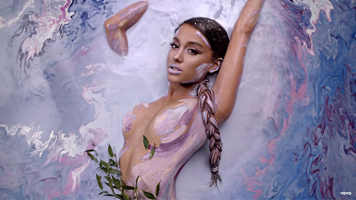 """Ariana Grande lying in a pool of multi-colored water with body paint for her """"God Is A Woman"""" music video."""