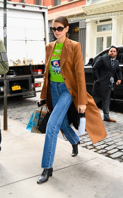 Kaia Gerber leaves the Michael Kors show during New York Fashion Week on February 12, 2020 while wearing a vibrant Marc Jacobs x Magda Archer intarsia jumper, Re/Done flare jeans, and a wool coat from Loewe.