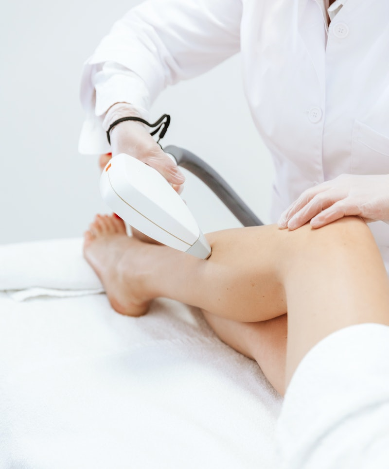 Woman getting laser hair removal on legs