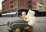 vintage photo of baby riding toy car with teddy bear