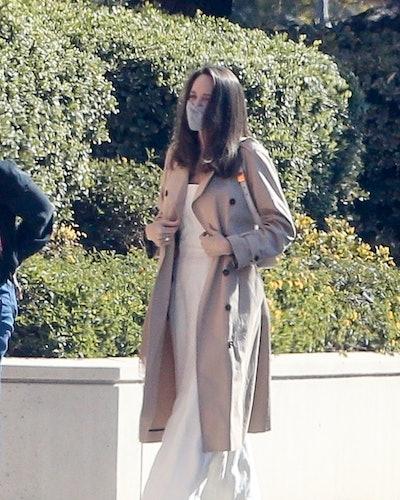 Angelina Jolie wearing a beige trench coat.