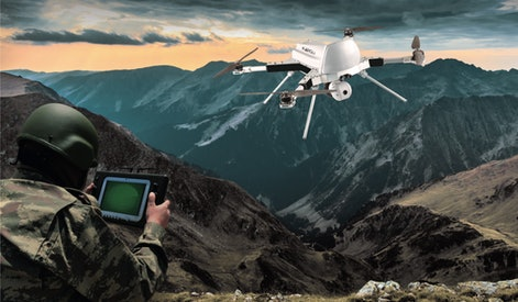 Soldier operating drone in mountainous region