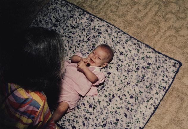 happy baby lying on baby mat on floor