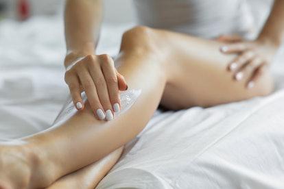 Woman applying cream to her legs