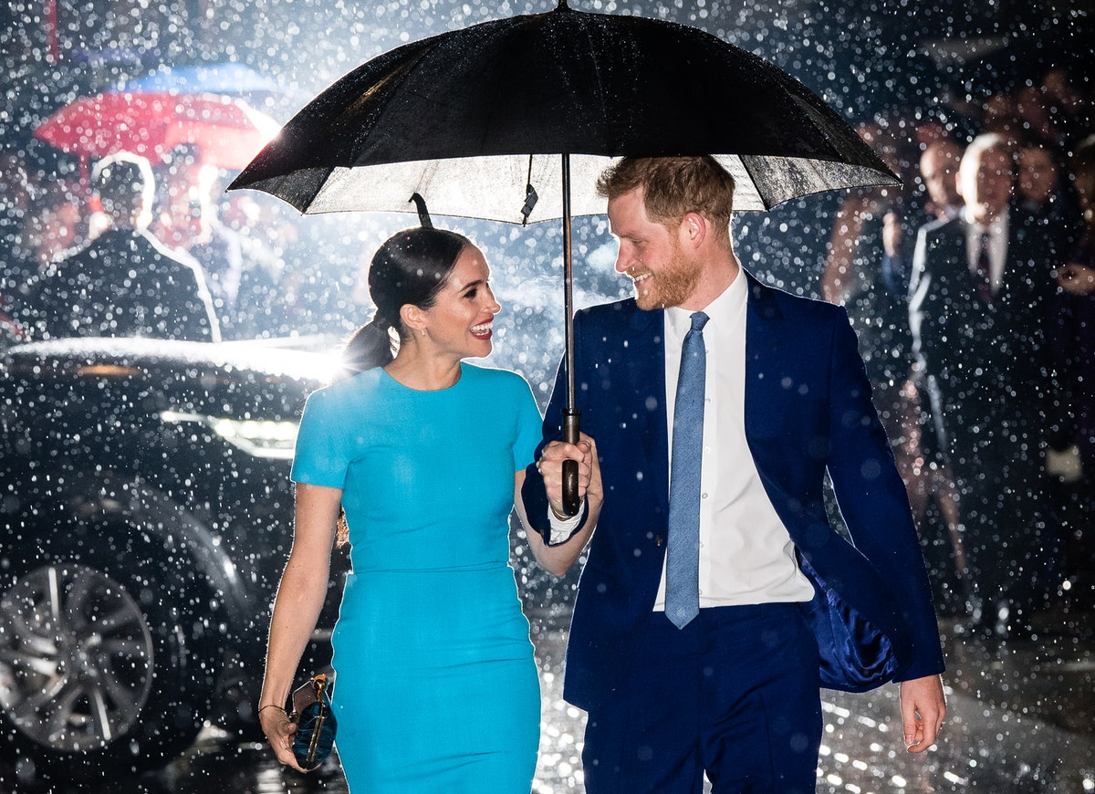 Prince Harry and Meghan Markle in the rain with umbrella.
