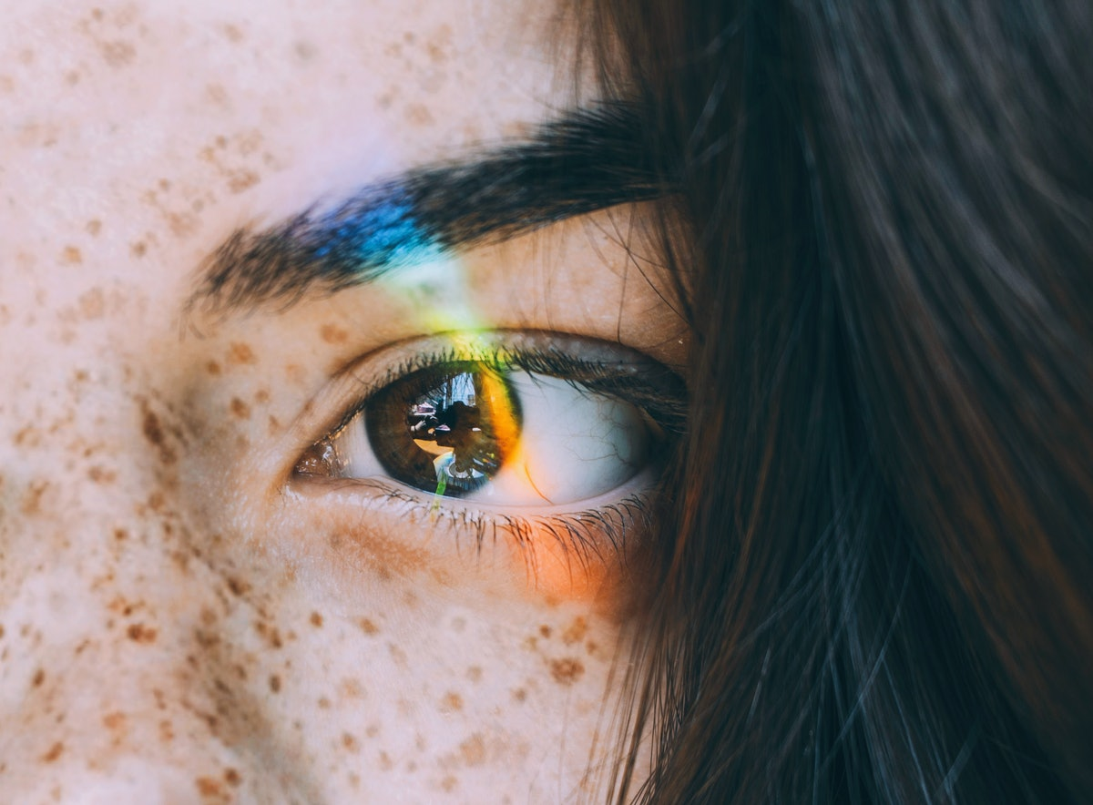 Young woman with rainbow light across eye to show when your dreams will be the most vivid, per your zodiac sign & the moon.