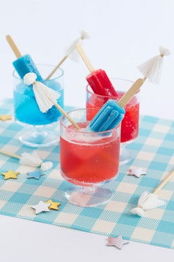 red, white, and blue cocktail made with a popsicle and tassel garnish