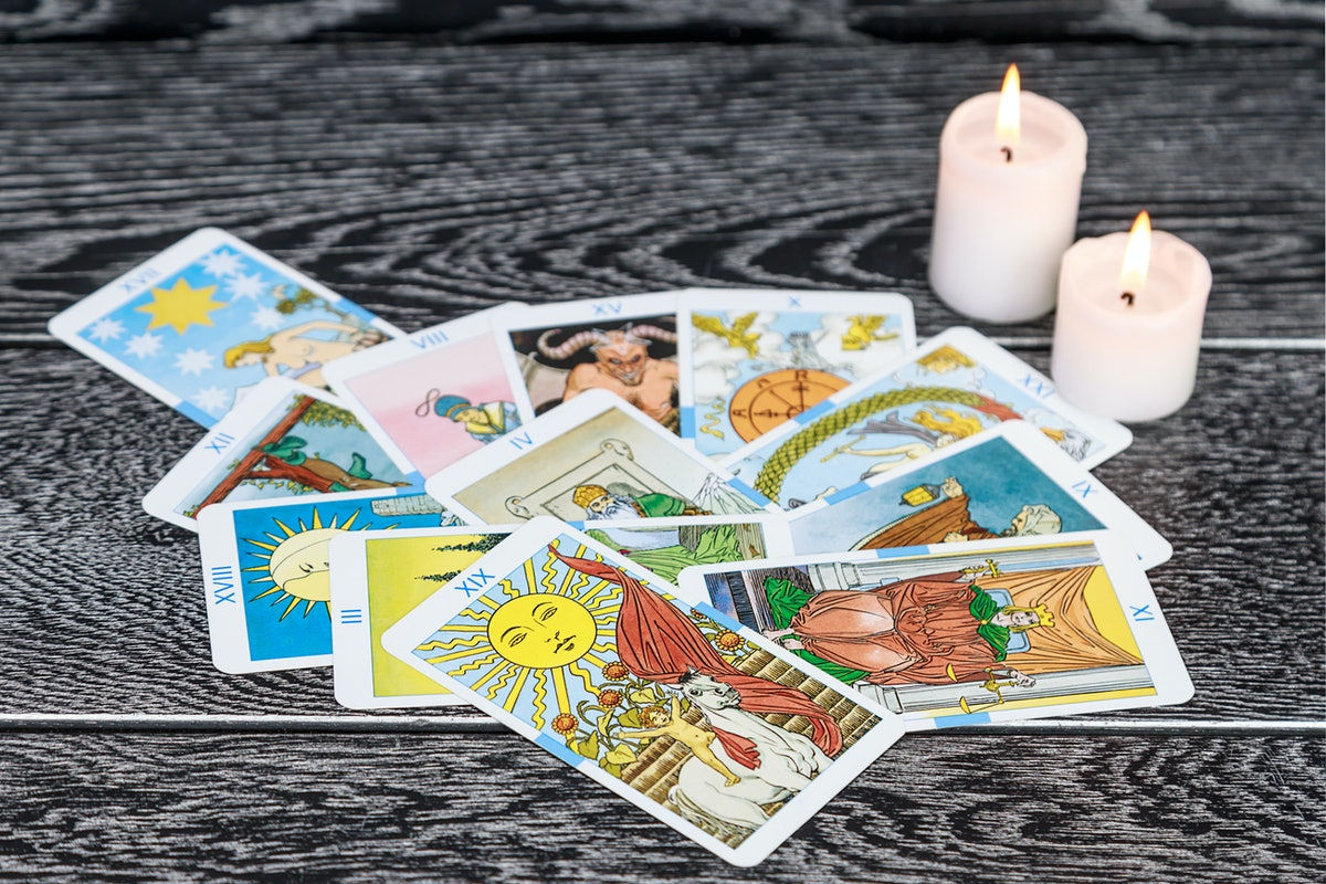 Set of tarot cards (as opposed to oracle decks) with candles.