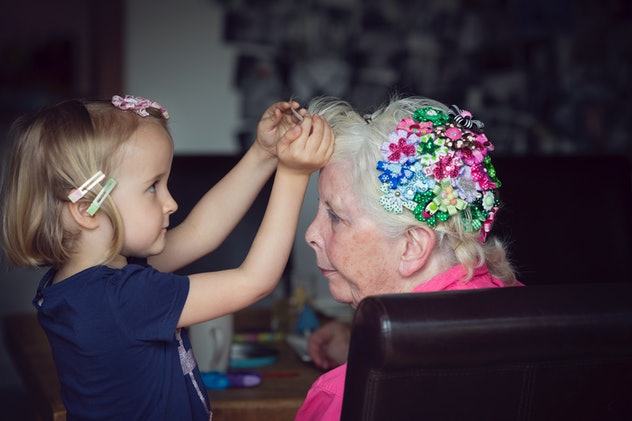 Grandchild decorating grandmother's hair