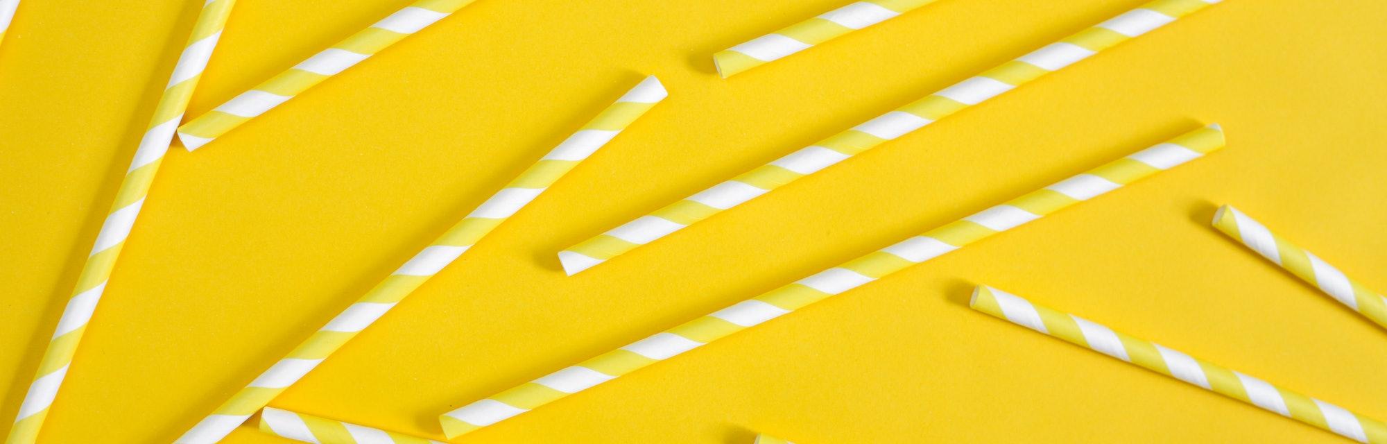 Single use plastic straws on yellow background