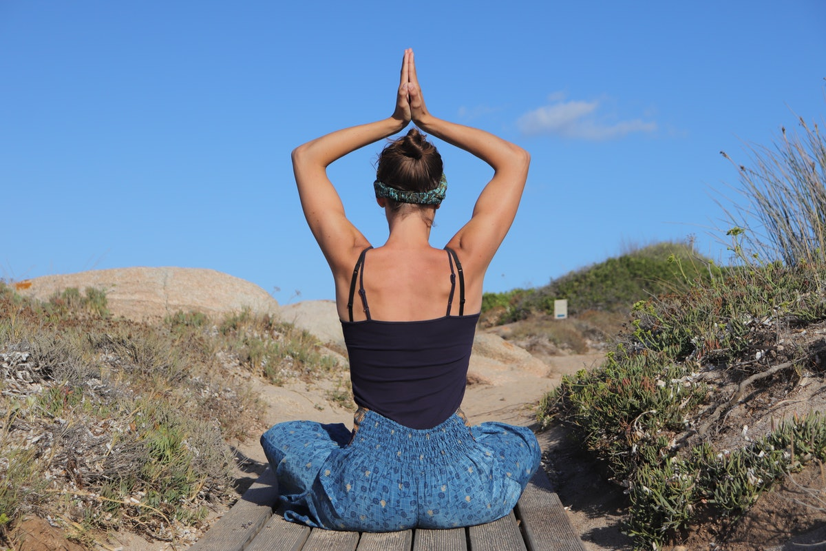 Young woman stretching her back — her zodiac sign body part — by meditating.