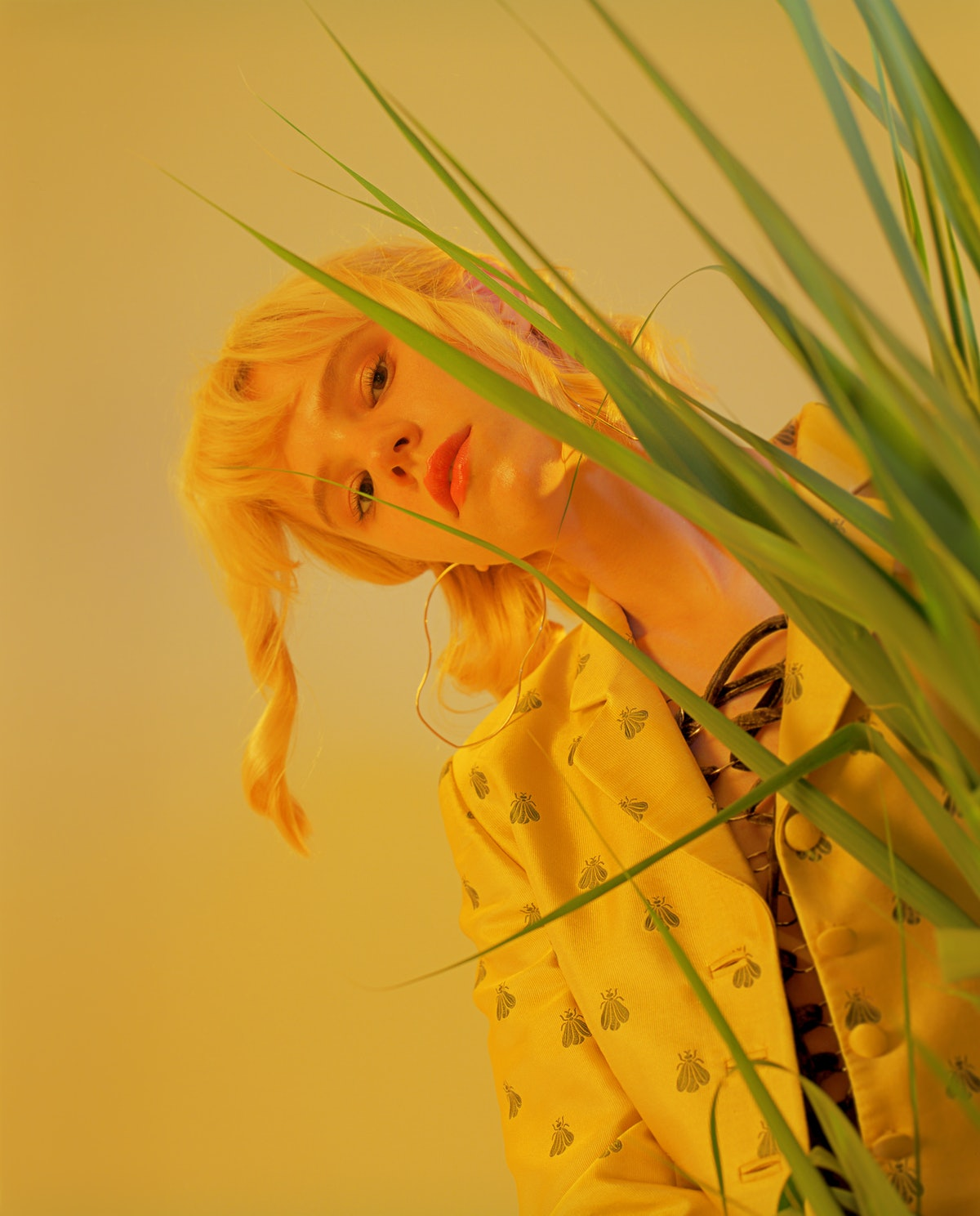Young Pisces woman peeking out from behind a plant because she's difficult to understand.
