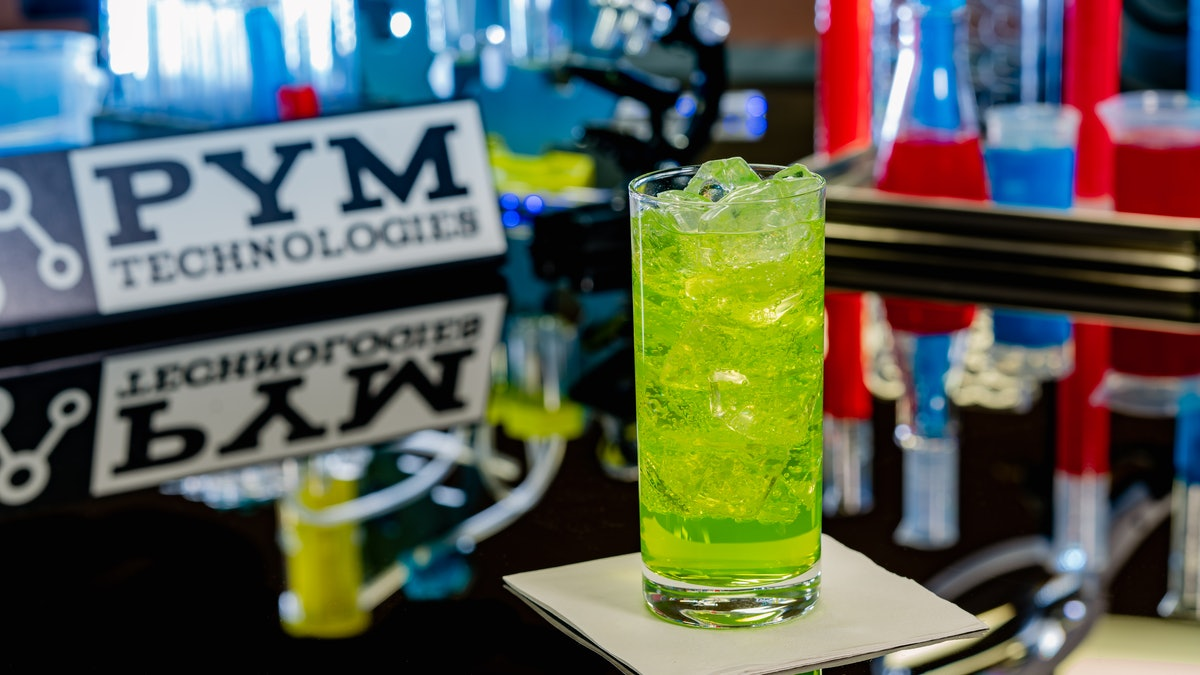 A glass of green Pingo Doce soda from Avengers Campus at Disneyland sits on a table and tastes like lemon-lime and vanilla.