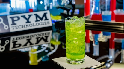 A glass of green Pingo Doce soda from Avengers Campus at Disneyland sits on a table and tastes like ...