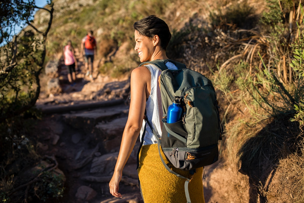 Young woman hiking, exercising her hips, thighs — her zodiac sign body parts.