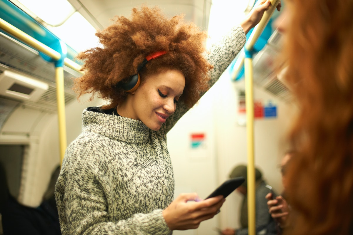 Young woman on the subway, texting her friends with a funny group chat name.