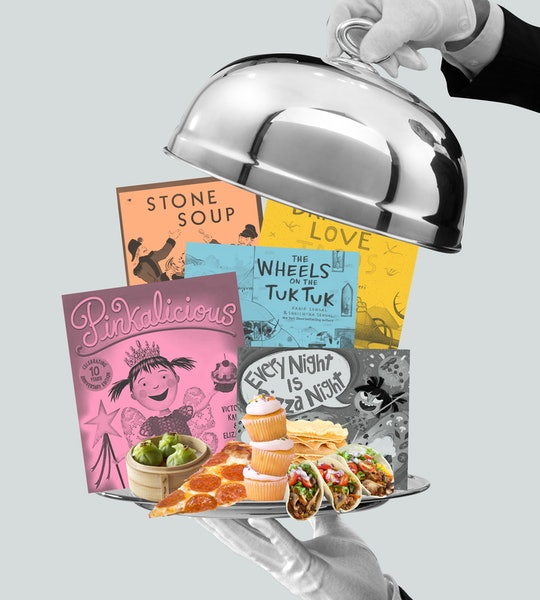 A white-gloved hand is holding a silver tray of children's books, including Pinkalicious, Every Night Is Pizza Night, and Stone Soup. Another hand is lifting the silver dome off the tray.