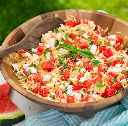 Wooden bowl of watermelon feta orzo salad on table