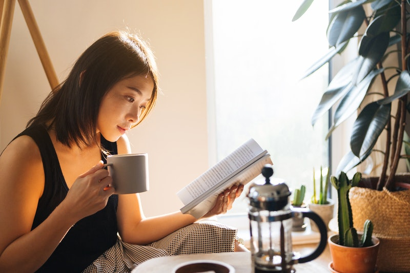 A woman reading with coffee.