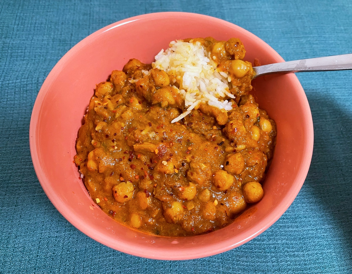 A bowl of chana masala on top of white rice.