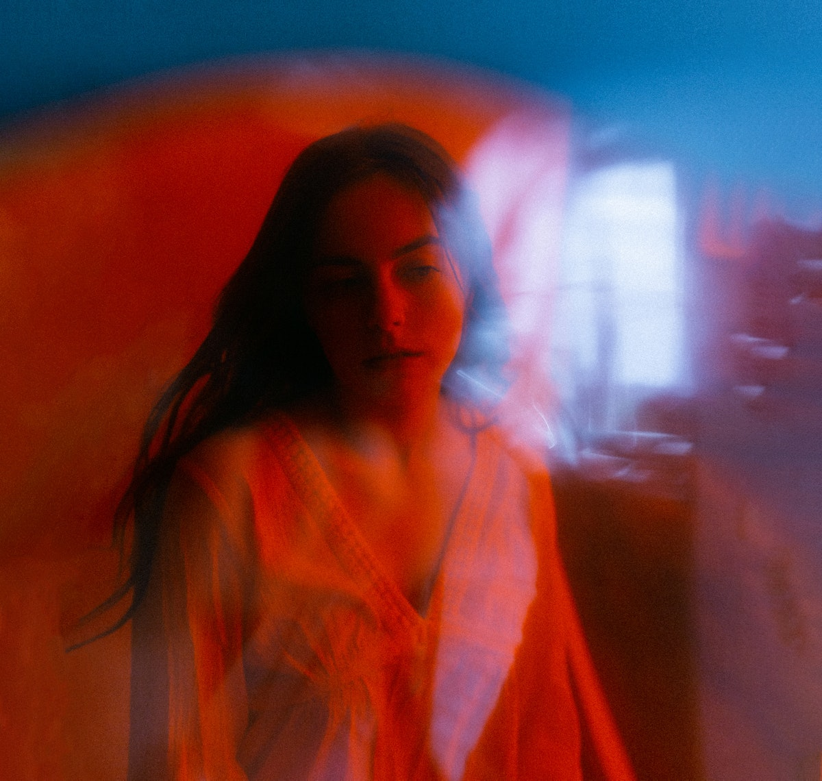 Young woman in red lighting wondering how the July 2021 new moon will affect her zodiac sign, per he...