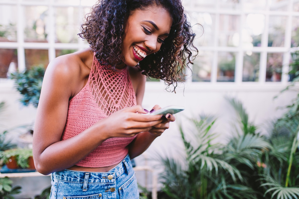 Young woman texting her best friend birthday wishes with plants in the background.