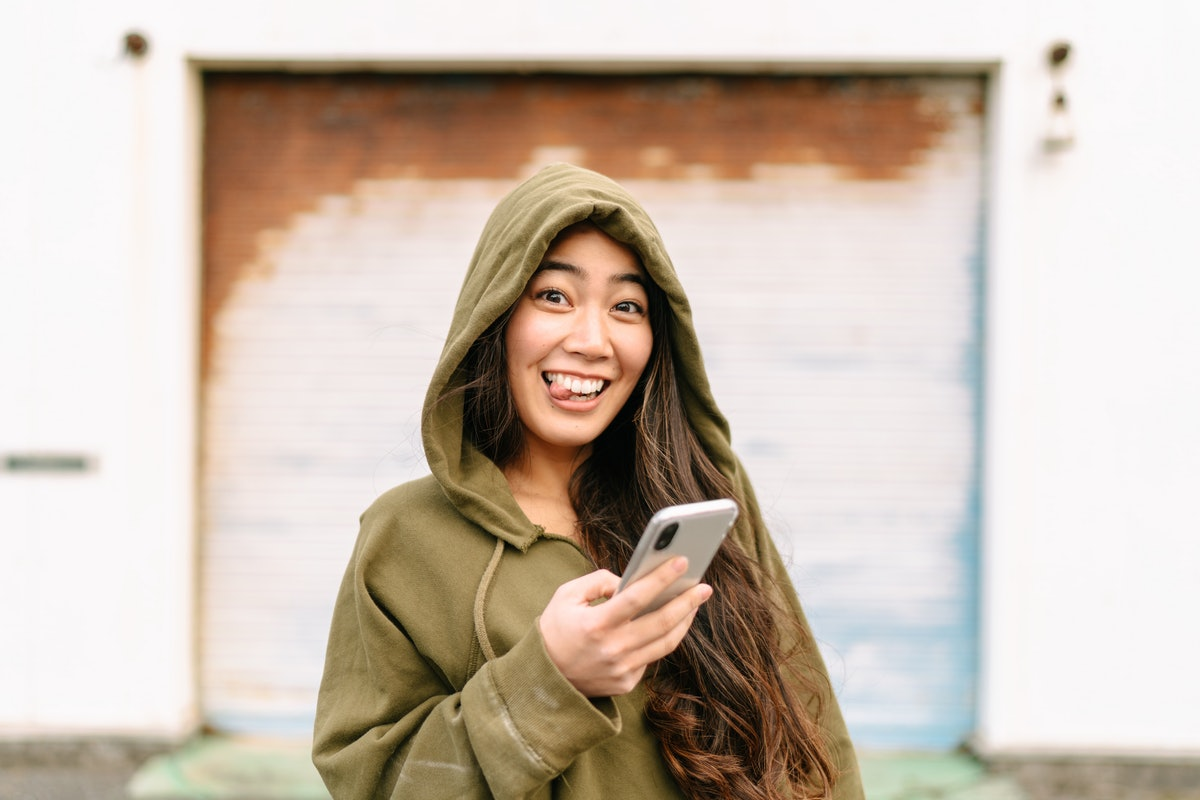 Young woman with her tongue sticking out after texting funny birthday wishes to her best friend.
