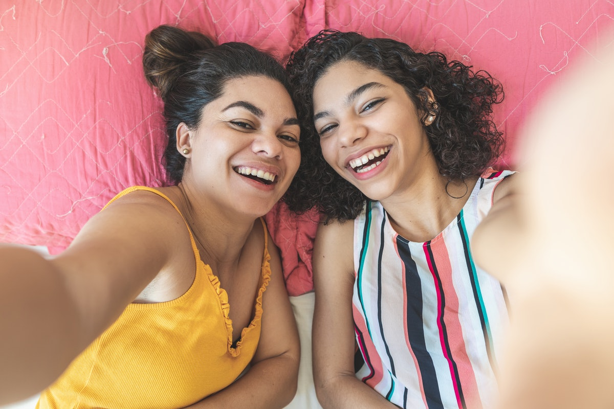 2 cousins taking a smiling selfie on a bed before posting a pic on Instagram with a cousin quote.