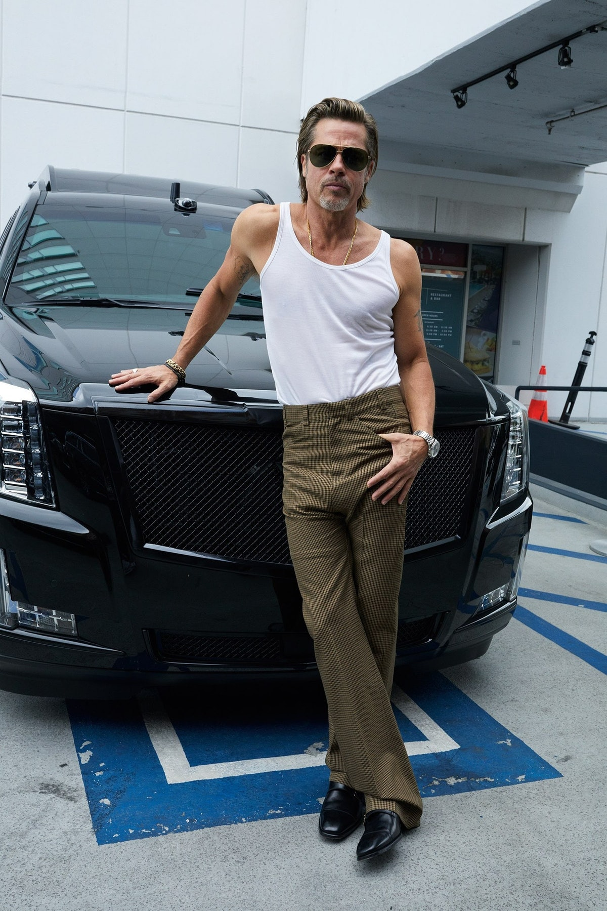Brad Pitt leaning on a car