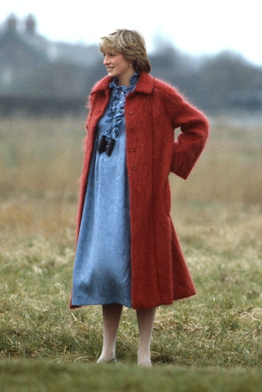 Princess Diana wearing a red coat in a field