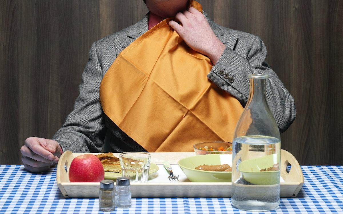Man with napkin tucked into collar.