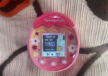 A Tamagotchi character is shown standing next to a sign that reads: Soup of the day, beer