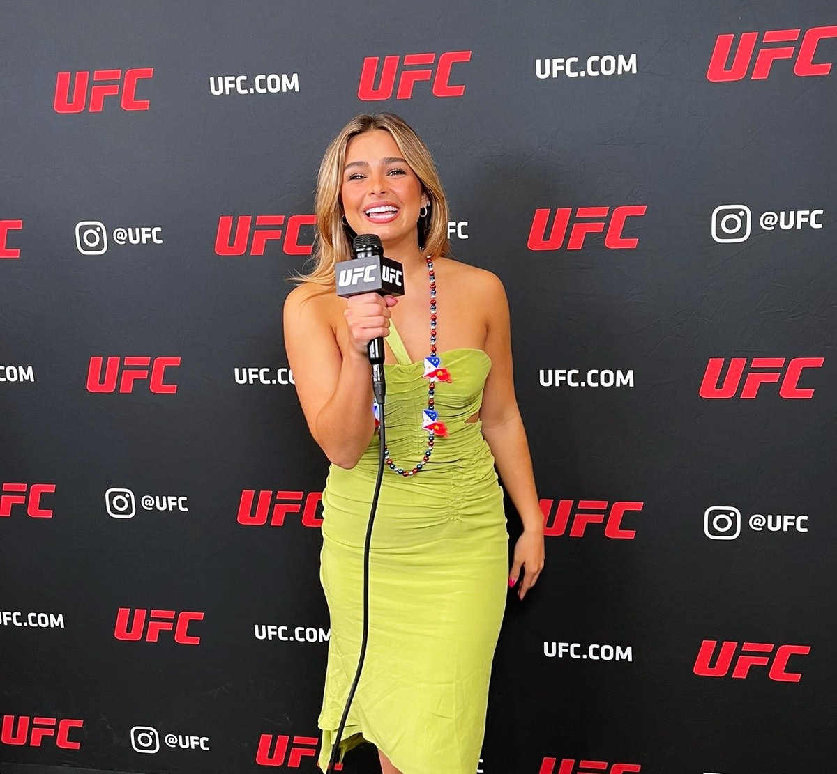 Addison Rae standing on a red carpet with UFC backdrop holding a mic.
