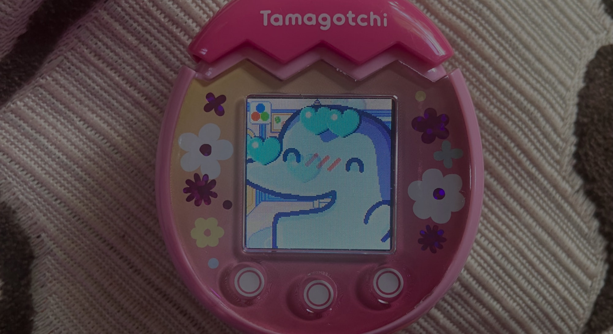 A pink Tamagotchi Pix is pictured with the character Ginjirotchi up close looking happy