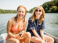 2 young friends out on the lake, having fun on a boat in need of Instagram captions for boating.