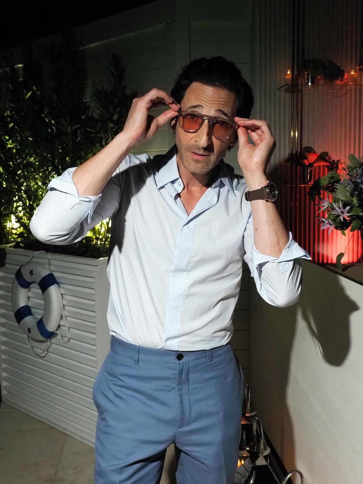 Adrien Brody touching his sunglasses
