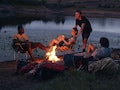 Young friends sitting around a bonfire at a campsite in need of Instagram captions.