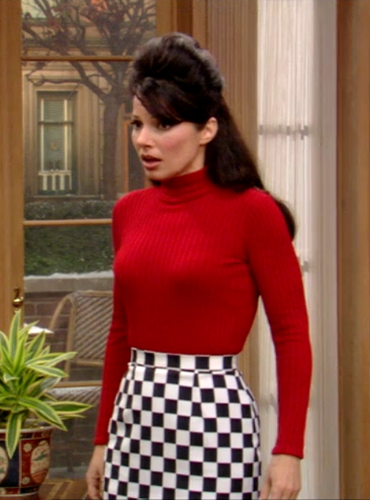 The Nanny's Fran Fine wearing a red long sleeve turtleneck tucked into a black and white checkerboar...
