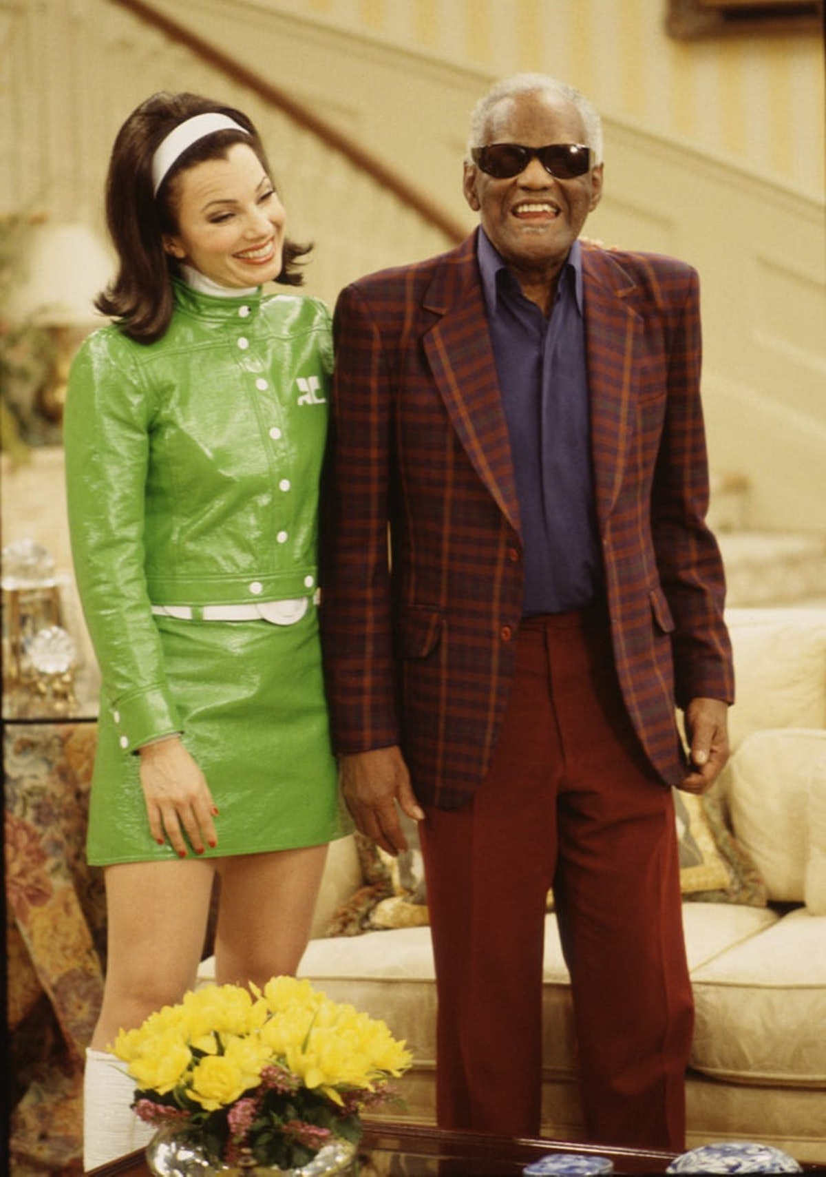 The Nanny's Fran Fine wearing a matching green jacket and skirt set with white gogo boots and a whit...