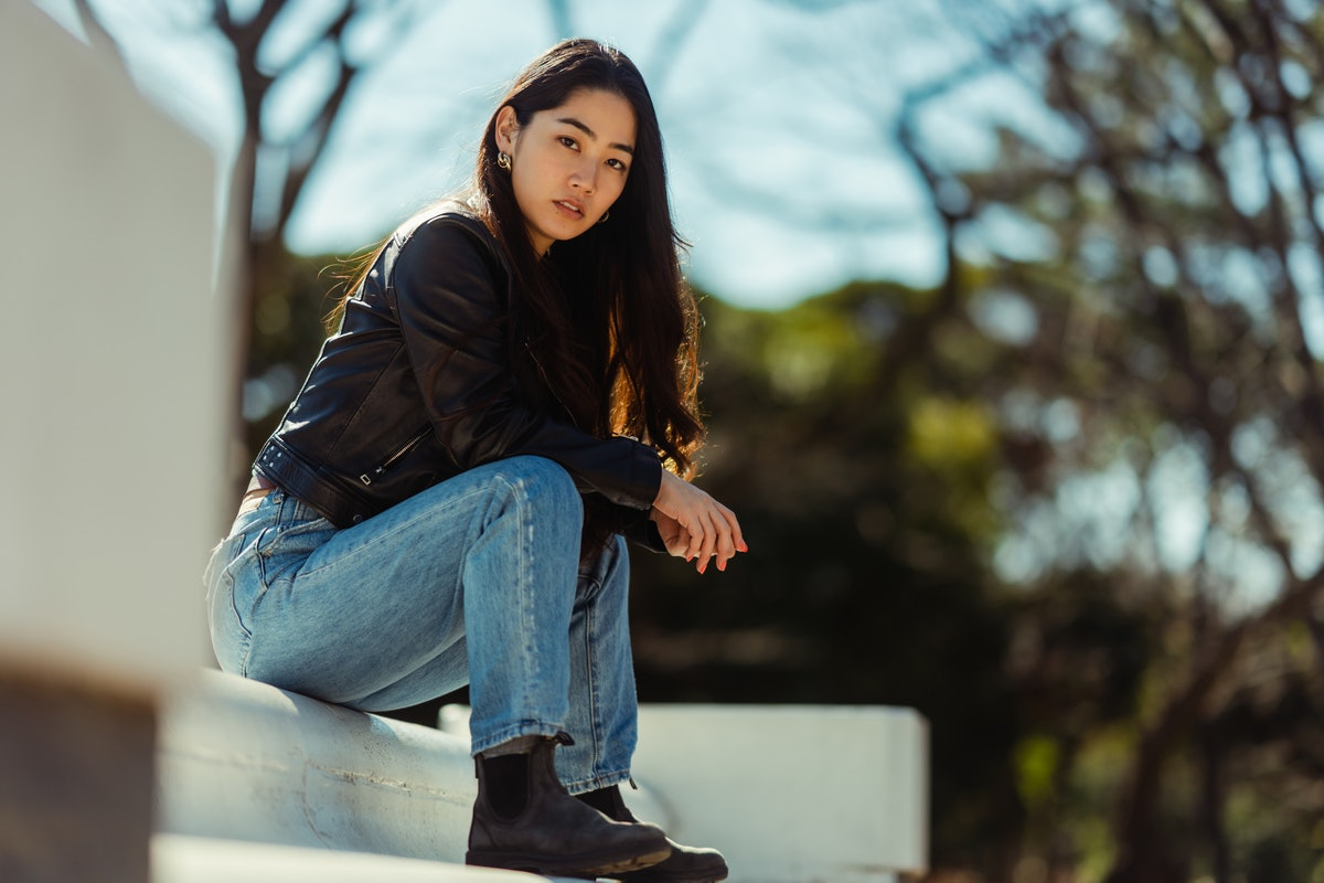Mad young woman sitting on a step, showing how she deals with anger, per her zodiac sign.